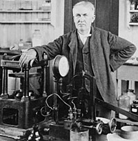 Thomas Edison standing near electrical equipment in his laboratory